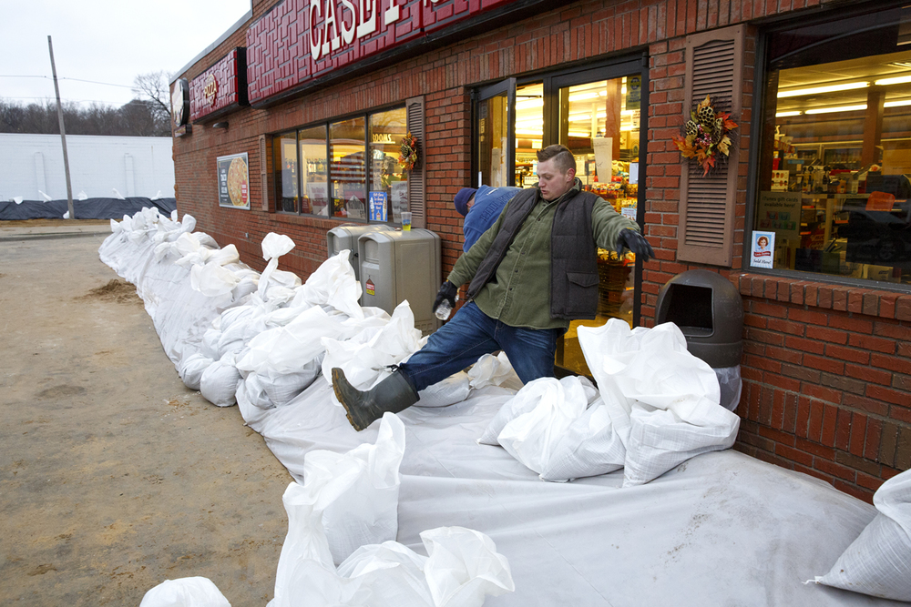 David Fritch, associate manager of the Casey's in Petersburg, climbs over a sand berm built to hold off approaching water from the Sangamon River, Wednesday, Dec. 30, 2015. Fritch and store manager Clayton A. Roberts closed and locked up the store, like many of the other businesses near the river. Rich Saal/The State Journal-Register