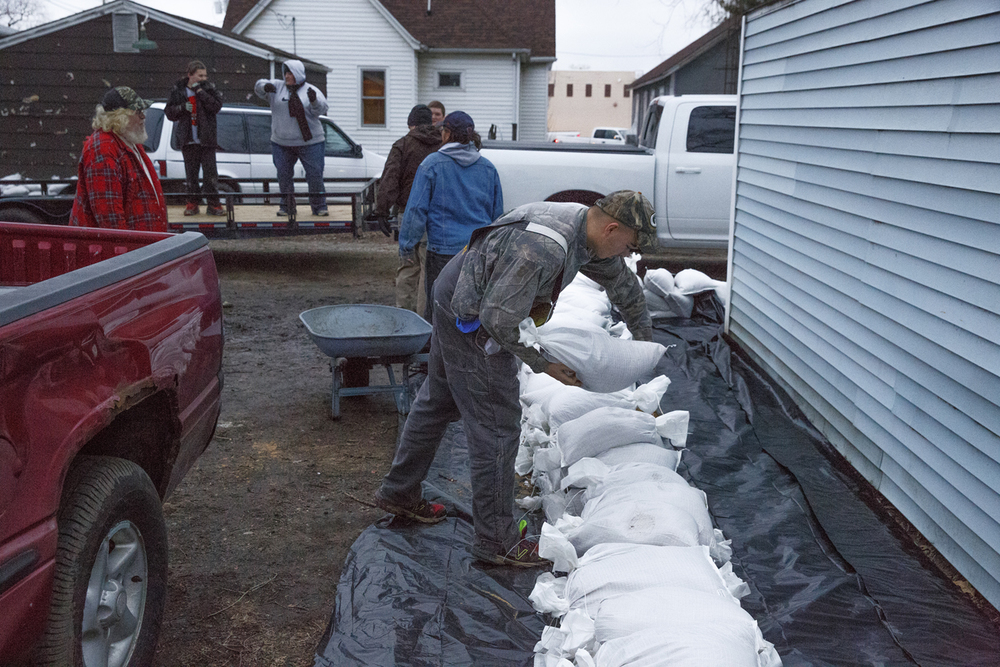 Tyler Guinan lays a sandbag near a home in Petersburg Wednesday, Dec. 30, 2015. Rich Saal/The State Journal-Register