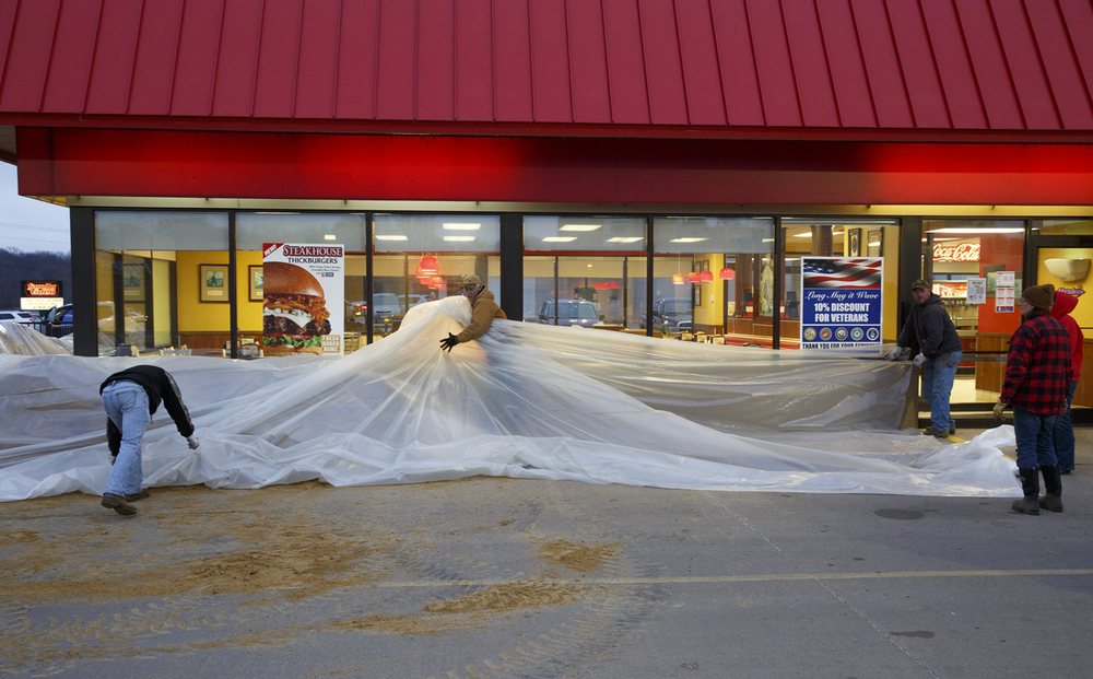 Employees of Weatherington Construction Co. build a sand berm around the Hardee's restaurant on Sangamon Street in Petersburg Wednesday, Dec. 30, 2015. Rich Saal/The State Journal-Register