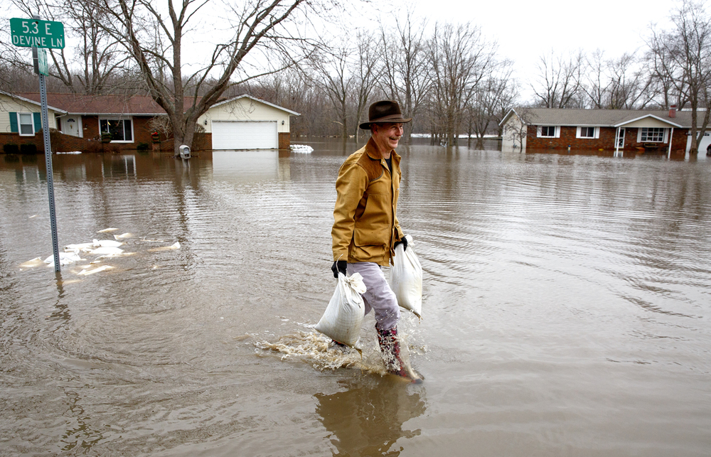 Mike Barrow moves sandbags that were in a pile on the street and had become submerged overnight, to his home on Paradise Lane in Spaulding Wednesday, Dec. 30, 2015. Rich Saal/The State Journal-Register