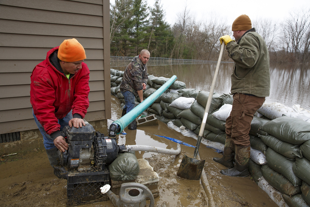 Jesse Williams, left, Ryan Daughtery and Alex Mercer pump water that had seeped under sandbags at the home of their friends, Dennis and Lindsey Griffitts, in Spaulding Wednesday, Dec. 30, 2015. Rich Saal/The State Journal-Register