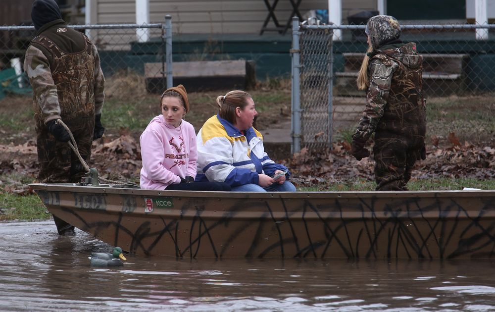 Annette Wilson at center and her niece Brittany Wilson prepare to reach dry land while seated in a boat while being pulled by rescue volunteers Missy and A.J. Devault along Springfield St. in Kincaid on Wednesday, Dec. 30, 2015. Annette said she was retrieving medical supplies and other necessary items needed by her mother-in-law, who evacuated from the home safely on Monday and is staying with her. In Kincaid, which sits near the South Fork of the Sangamon River, floodwaters closed a section of Illinois 104, with a section of homes in South Kincaid along Springfield St. surrounded by water cut off. Volunteers using atv's ferried supplies into the area for homes that still had power not affected by the flooding.  David Spencer/The State Journal-Register