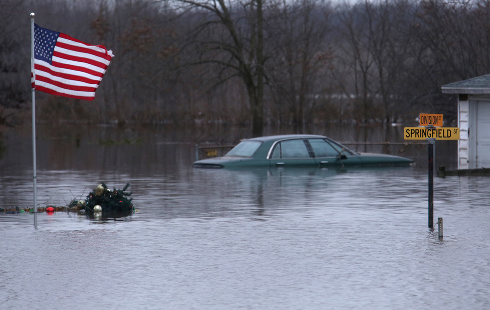 A submerged automobile can be seen in front of a residence at the intersection of Division and Springfield streets along with submerged Christmas decorations snagged on the base of the American flag seen in Kincaid on Wednesday, Dec. 30, 2015. In Kincaid, which sits near the South Fork of the Sangamon River, floodwaters closed a section of Illinois 104, with a section of homes in South Kincaid along Springfield St. surrounded by water cut off. Volunteers using atv's ferried supplies into the area for homes that still had power not affected by the flooding.  David Spencer/The State Journal-Register