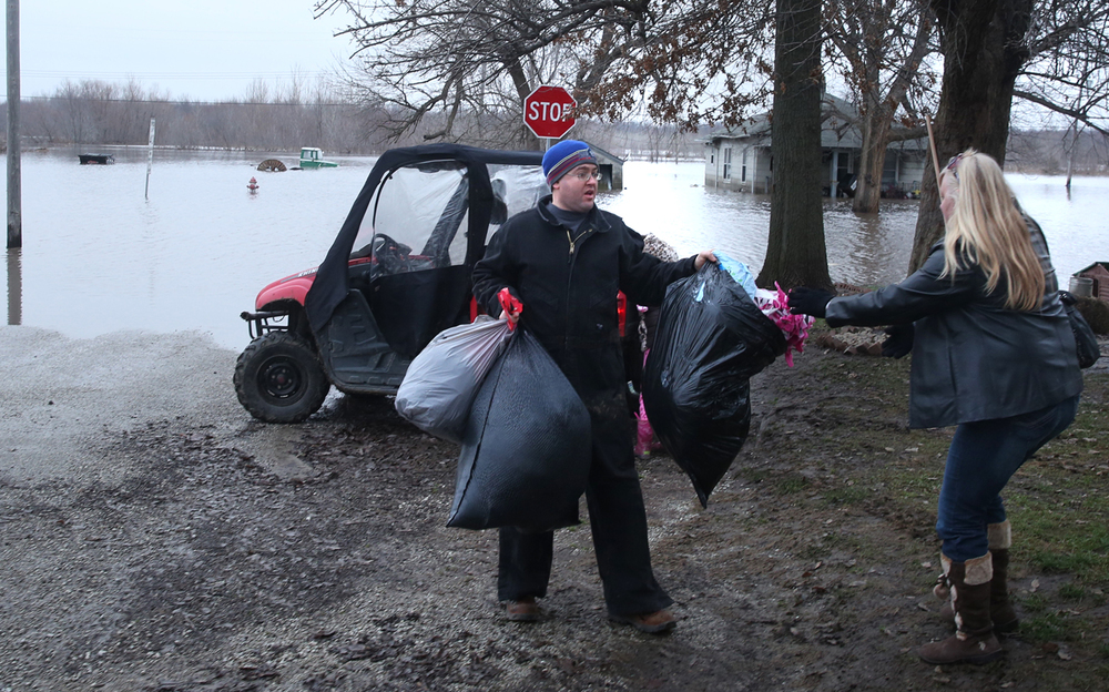 Anthony Price of Morrisonville passes off bags of supplies to Jessica Rabideau, a long-time resident of South Kincaid, who is temporarily cut off from flood waters at right on Wednesday, Dec. 30, 2015. In Kincaid, which sits near the South Fork of the Sangamon River, floodwaters closed a section of Illinois 104, with a section of homes in South Kincaid along Springfield St. surrounded by water cut off. Volunteers using atv's ferried supplies into the area for homes that still had power not affected by the flooding.  David Spencer/The State Journal-Register