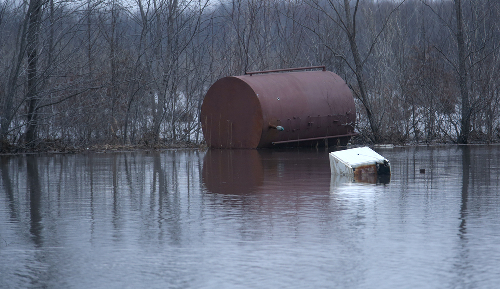 A large oil tank and refrigerator float in flood waters north of Springfield St. in Kincaid on Wednesday, Dec. 30, 2015. In Kincaid, which sits near the South Fork of the Sangamon River, floodwaters closed a section of Illinois 104, with a section of homes in South Kincaid along Springfield St. surrounded by water cut off. Volunteers using atv's ferried supplies into the area for homes that still had power not affected by the flooding.  David Spencer/The State Journal-Register