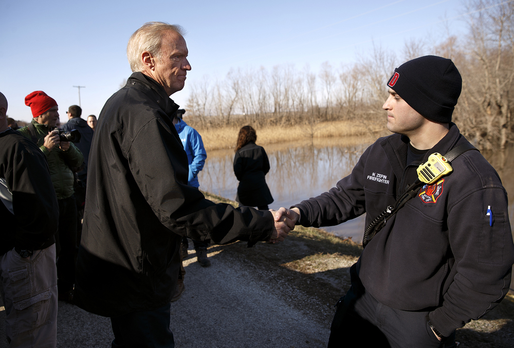 Illinois Gov. Bruce Rauner thanked Taylorville firefighter Nicholas  Zepin and other rescue workers after making remarks at  1700 North Road in Kincaid near where the body of Brandon M. Mann, 18, of Taylorville was found Sunday, Jan. 3, 2016. Sunday's discovery marks the fourth confirmed death in Christian County due to the flood, which began after central Illinois endured three days worth of rain last week. Ted Schurter/The State Journal-Register