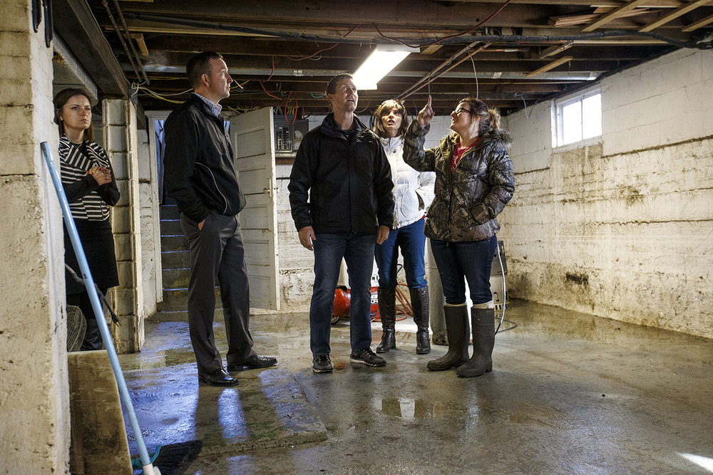 Angel Rabideau shows, from left, Illinois state Rep. Avery Bourne, R-Raymond, State Sen. Andy Manar, D-Bunker Hill, U.S. Rep. Rodney Davis, R-Taylorville  and State Rep. Sue Scherer, D-Decatur, the flood-damaged basement of her Kincaid home Sunday, Jan. 3, 2015. Ted Schurter/The State Journal-Register