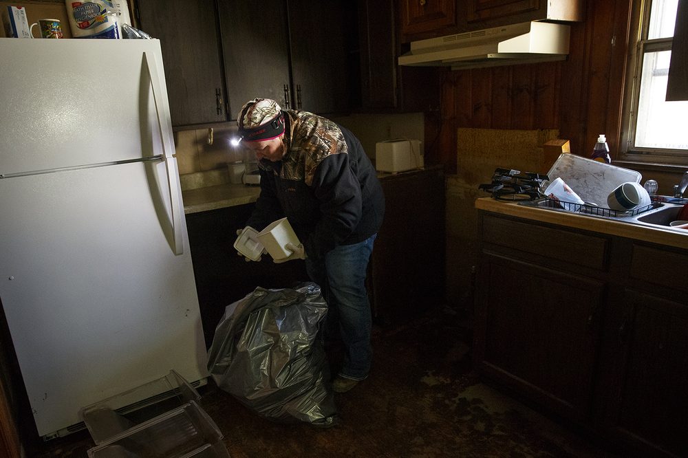Annette Wilson cleans out the kitchen of her mother-in-law Lottie Wilson's flood-damaged Kincaid home Sunday, Jan. 3, 2015.  Ted Schurter/The State Journal-Register