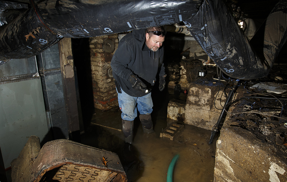 Jason Dees examines the foundation of Lottie Wilson's flooded Kincaid home as he helps pump out the basement of Sunday, Jan. 3, 2015. Dees said he hasn't seen this kind of flooding in 40 years of living in the area. Ted Schurter/The State Journal-Register