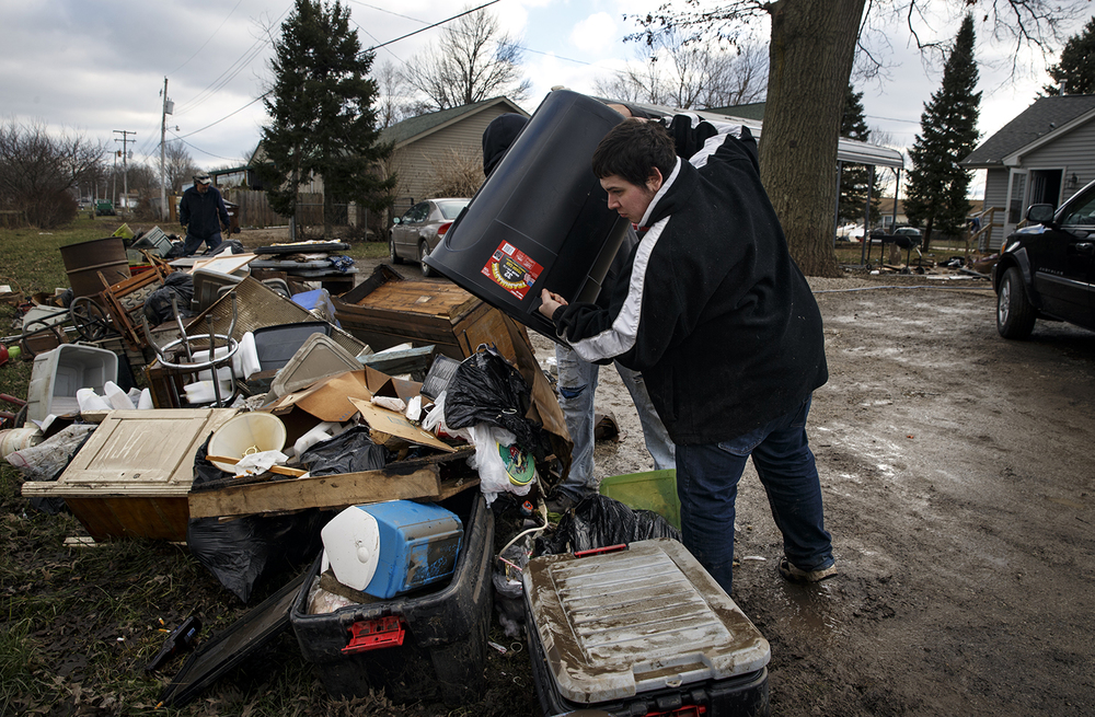 Eric Humes dumps debris onto a trash pile behind a flood-damaged Kincaid home Sunday, Jan. 3, 2015. Ted Schurter/The State Journal-Register