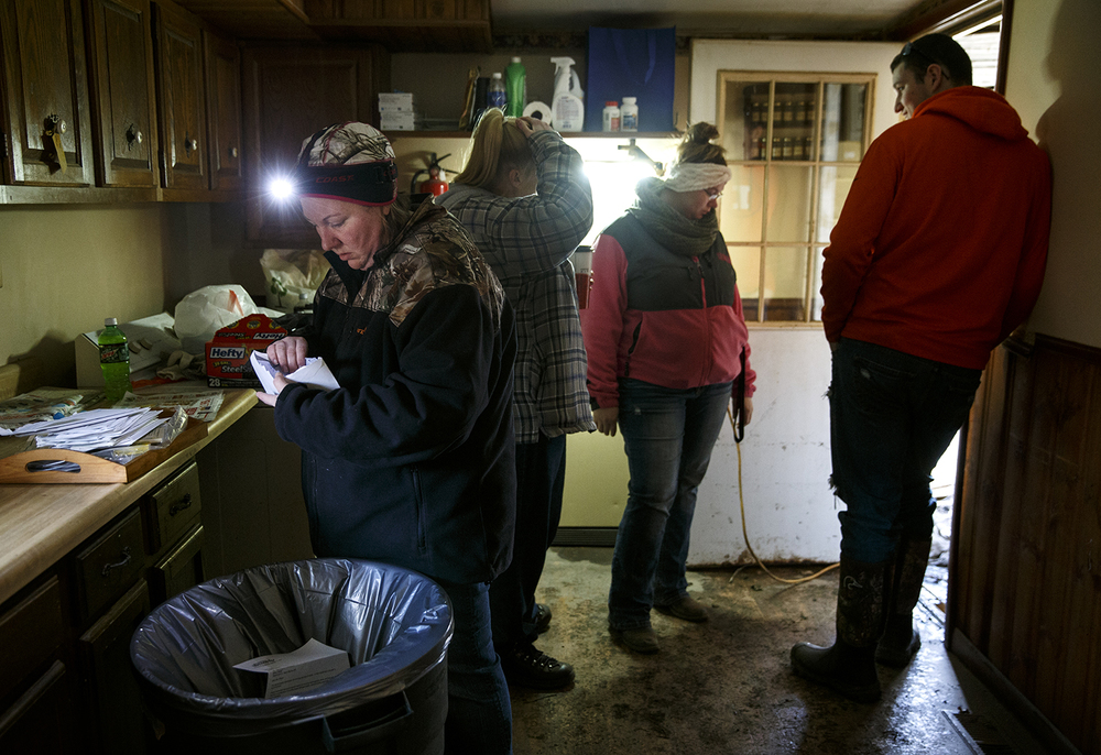 Annette Wilson sorts through items in the kitchen of her mother-in-law Lottie Wilson's flood-damaged Kincaid home Sunday, Jan. 3, 2015. Ted Schurter/The State Journal-Register