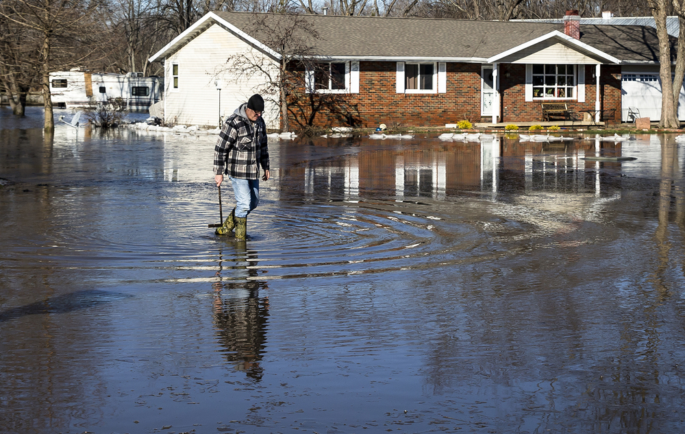 Kip Troeger walks through flood waters to assess the depth to see if he could get his car out of the garage of his home on Devine Drive in the Holiday Estates Subdivision, Saturday, Jan. 2, 2016, near Spaulding, Ill. Flood waters inundated the neighborhood from Wolf Creek that connects to the nearby Sangamon River. Justin L. Fowler/The State Journal-Register