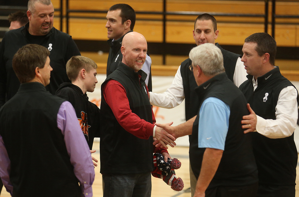 In a show of solidarity for former Waverly High School coach Bill Pool, center, who is battling cancer, the head coaches of teams playing in the Waverly Holiday Baskteball Tournament wore black sweater vests for a group photo taken between games Monday, Dec. 28, 2015.  The sweater vest is a Pool fashion trademark at the tournament. David Spencer/The State Journal-Register