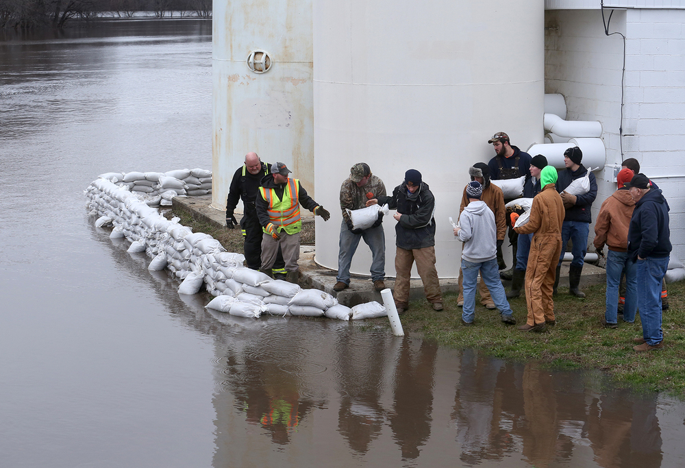 Volunteers with area fire departments Village of Dawson employees build a sandbag wall around the Dawson water treatment plant on the Mechanicsburg blacktop Tuesday, Dec. 29, 2015. Heavy rain over the weekend brought the river up two feet over flood stage to 27�, 5� threatening the plant. David Spencer/The State Journal-Register