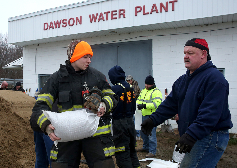 Dawson volunteer firefighter Nicole Reese passes a sandbag to Dawson resident Tony Prytherch at the Dawson water plant Tuesday, Dec. 29, 2015. The plant was in danger of flooding from the Sangamon River after heavy rains over the weekend. David Spencer/The State Journal-Register