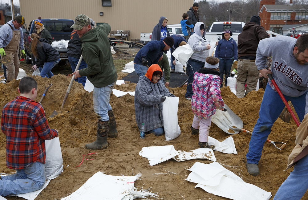 Community volunteers fill sandbags near Sangamon Street in Petersburg Wednesday, Dec. 30, 2015. Rich Saal/The State Journal-Register