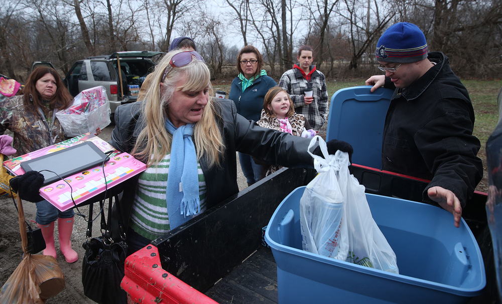Jessica Rabideau, a long-time resident of South Kincaid, loads supplies into a tub in the bed of an atv owned by rescue volunteer Anthony Price of Morrisonville at right. Kincaid, along with other volunteers seen in the background, was helping land-locked residents ferry supplies into the area until waters recede enough on Wednesday, Dec. 30, 2015. In Kincaid, which sits near the South Fork of the Sangamon River, floodwaters closed a section of Illinois 104, with a section of homes in South Kincaid along Springfield St. surrounded by water cut off. Volunteers using atv's ferried supplies into the area for homes that still had power not affected by the flooding.  David Spencer/The State Journal-Register