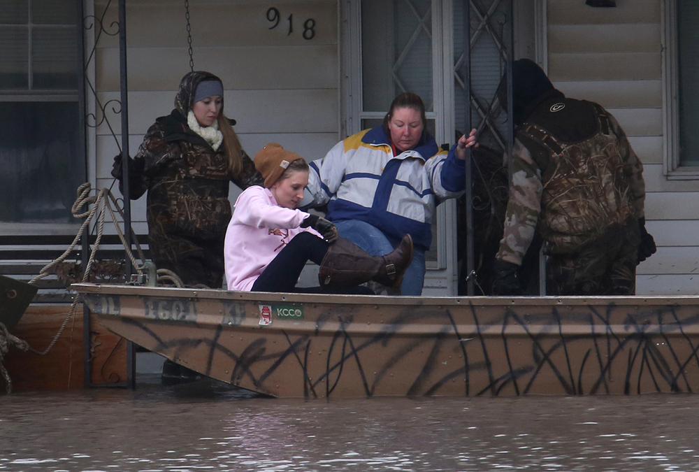 Annette Wilson at center and her niece Brittany Wilson are assisted into a boat by rescue volunteers Missy and A.J. Devault in front of Annette Wilson's mother-in-law's home in the 900 block of Springfield St. on Wednesday, Dec. 30, 2015. Annette said she was retrieving medical supplies and other necessary items needed by her mother-in-law, who evacuated from the home safely on Monday and is staying with her. In Kincaid, which sits near the South Fork of the Sangamon River, floodwaters closed a section of Illinois 104, with a section of homes in South Kincaid along Springfield St. surrounded by water cut off. Volunteers using atv's ferried supplies into the area for homes that still had power not affected by the flooding.  David Spencer/The State Journal-Register