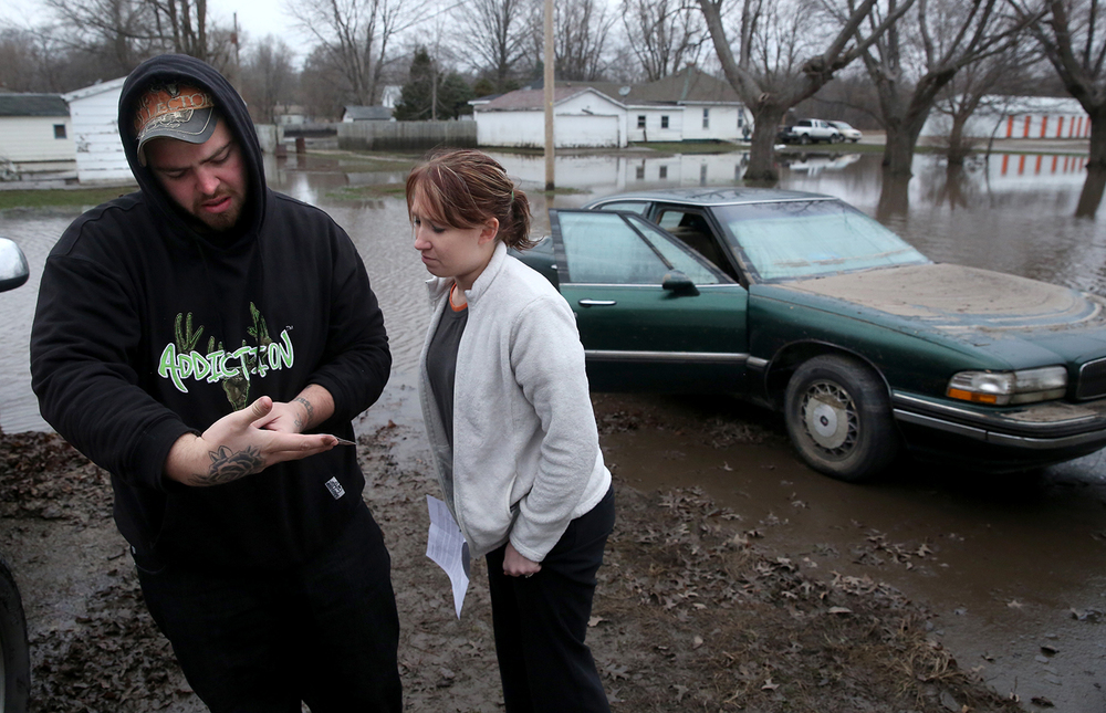 Kincaid residents Thomas Barnard and his fiancée Jessica Klick inspect the registration for Klick's 1995 Buick seen behind them which was nearly completely submerged in floodwaters from the South Fork of the Sangamon River during the couple's first visit back to their home after water receded on Thursday, Dec. 31, 2015.  David Spencer/The State Journal-Register