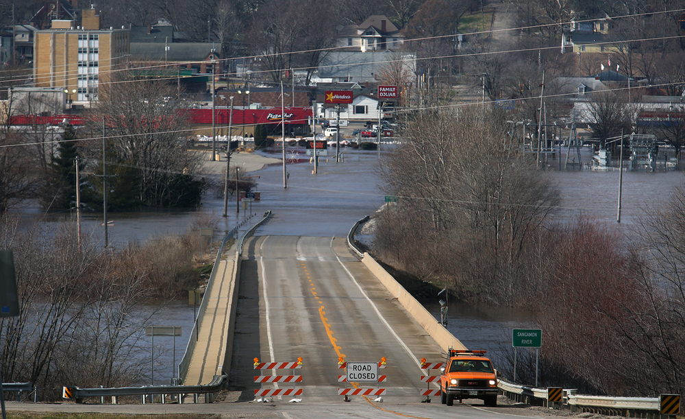 Out of its banks, the Sangamon River cuts off traffic to Petersburg from the east on Illinois 123 Friday, Jan. 1, 2016. Although water covered Sangamon Street and threatened some merchants, Petersburg mayor John Stiltz said his town dodged a bullet thanks to a five-block long emergency levee built by volunteers. David Spencer/The State Journal-Register