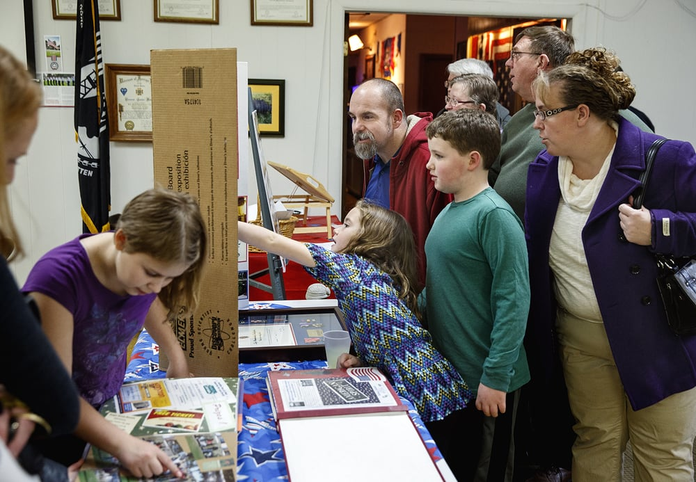 Guests look at photographs and memorabilia of Marine Staff Sgt. Roger Gross who died in November, nearly ten years after being injured in an IED explosion near Baghdad, Iraq, during a celebration of his life at the Veterans of Foreign Wars Post 755 Saturday, Jan. 9, 2016. Ted Schurter/The State Journal-Register