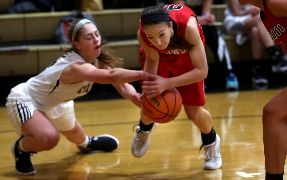 Titans player Ciara Lahr holds onto the ball while Cyclones player Anna Lowis gets a hand on it during first half play. David Spencer/The State Journal Register