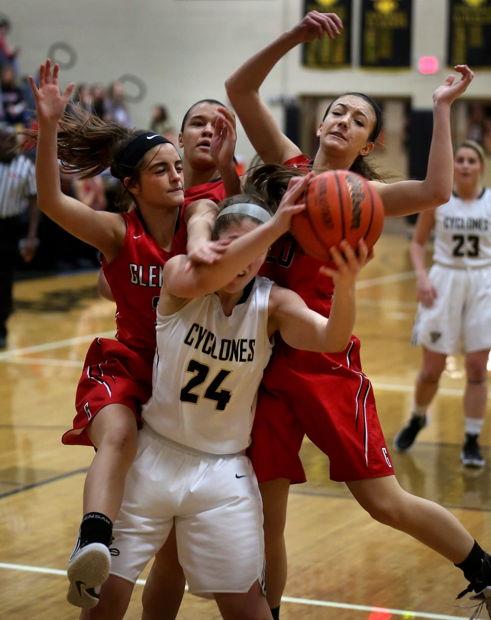 After grabbing a rebound, Cyclones player Anna Lowis is surrounded by Titan defenders from left to right: Lexie Iacono, Kiara Downey, Ciara Lahr. David Spencer/The State Journal Register