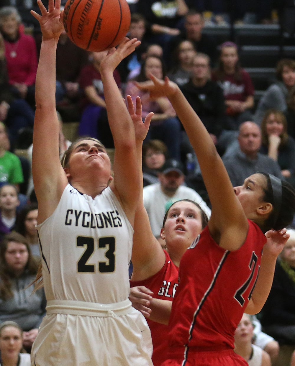 Cyclones player Kenzie Trees tries to put up a shot late in the game while being defended by Titan players Makenzie Bray at center and Kiara Downey. David Spencer/The State Journal Register