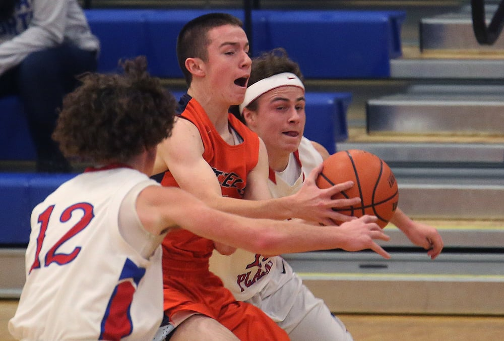 New Berlin player Ben Butcher is sandwiched by Pleasant Plains defenders Daulton Nibbe at left and Cole Greer while trying to keep control of the ball. David Spencer/The State Journal Register