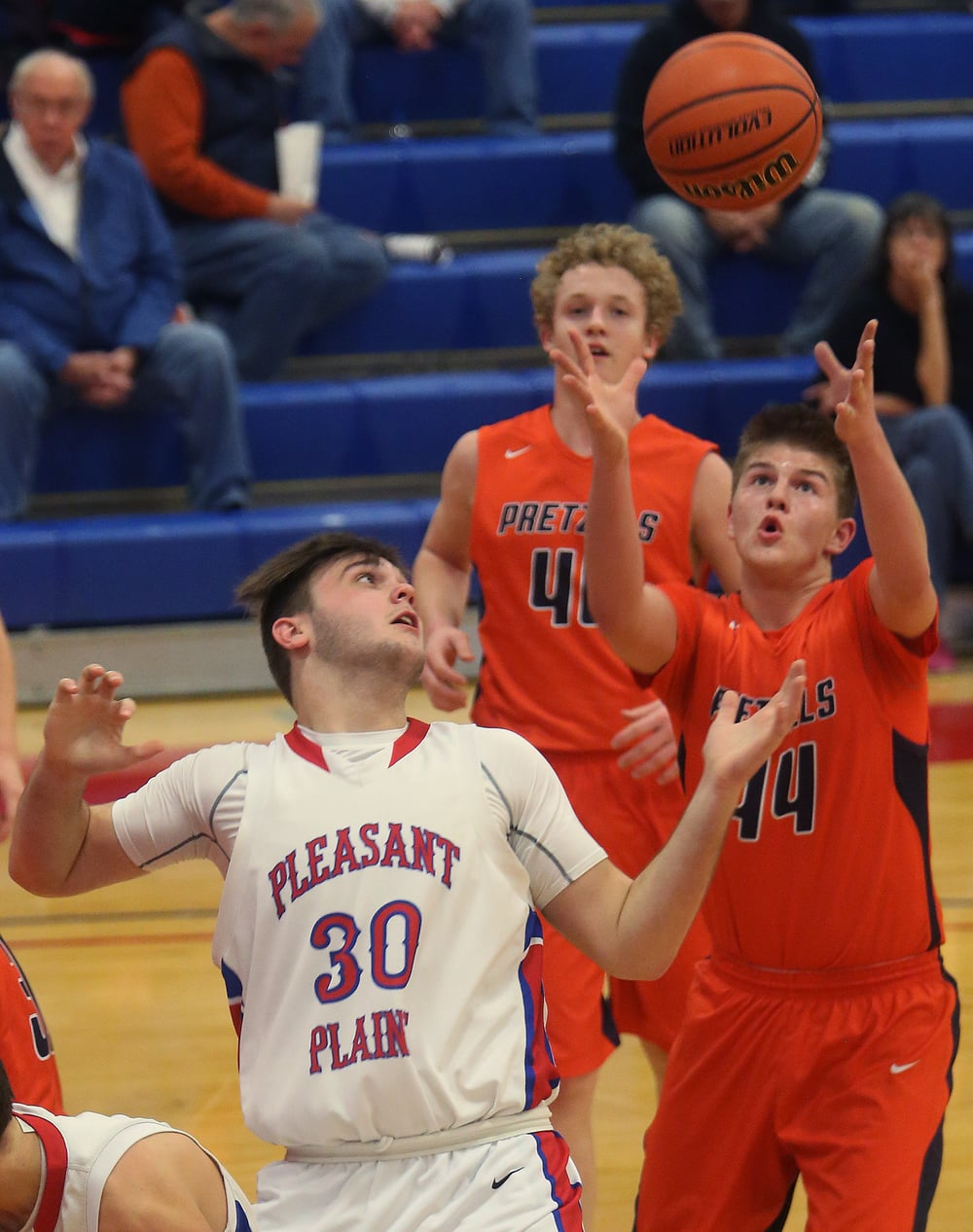 New Berlin player Casey Bixby prepares to snag a rebound while Pleasant Plains player Austin Finley looks on at left. David Spencer/The State Journal Register