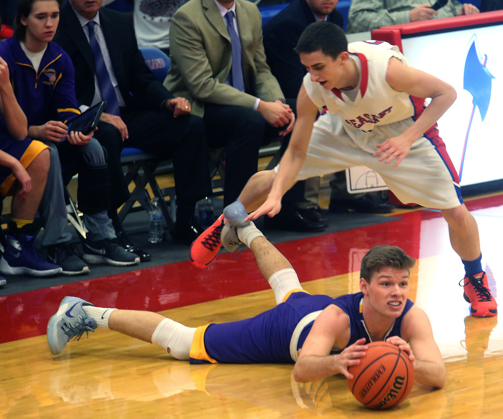 Williamsville player Jacob Sexton looks to see if he can pass while prone on the court while Plains defender Isaac Collins prepares to hurdle over him. David Spencer/The State Journal Register