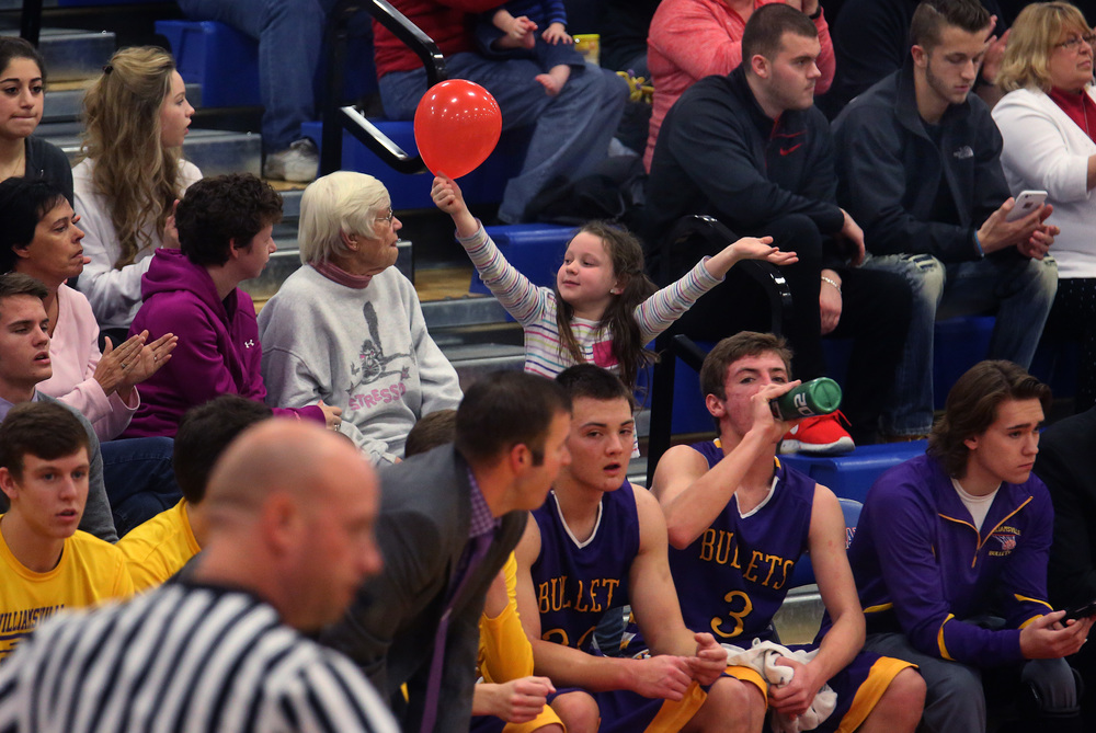 On the Cardinals fans side: a young fan cheers with her red balloon behind the Williamsville bench. David Spencer/The State Journal Register