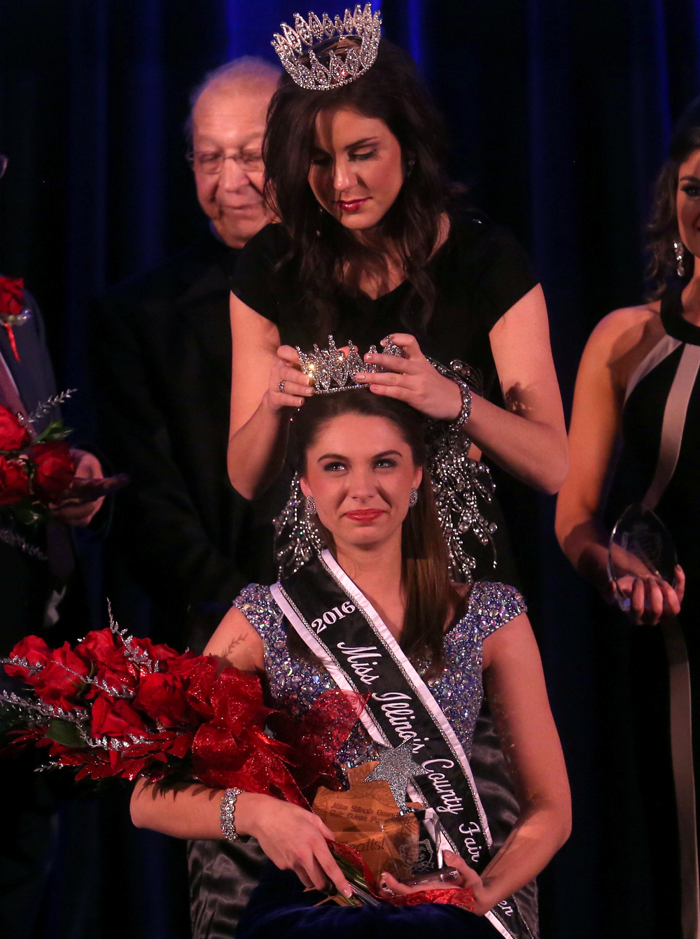 2016 Miss Illinois County Fair queen Abby Foster of Vermilion County has her tiara secured by outgoing 2015 Miss Illinois County Fair Queen Sadie Gassmann. David Spencer/The State Journal-Register