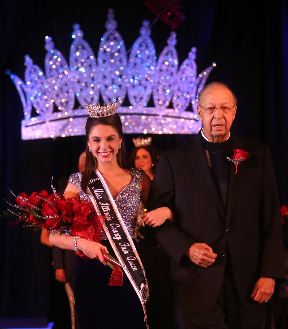 Illinois Department of Agriculture Director Raymond Poe escorts 2016 Miss Illinois County Fair queen Abby Foster of Vermilion County off the stage late Sunday night. David Spencer/The State Journal-Register