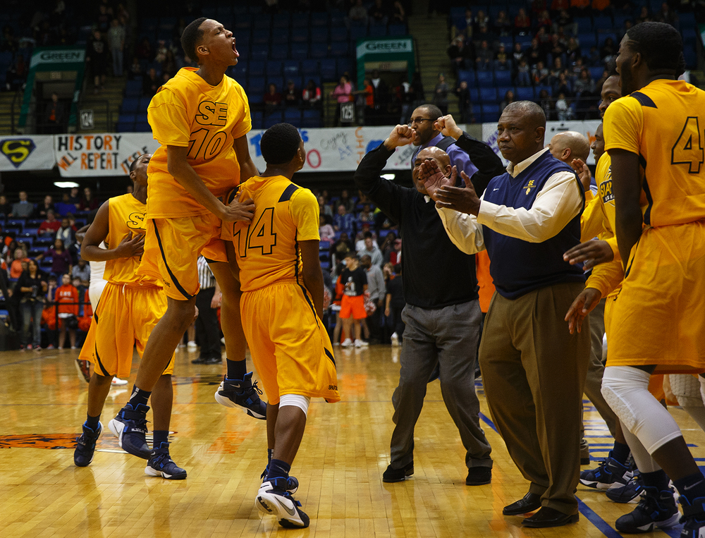Southeast's Isaiah Walton leaps into the air to celebrate the Spartans victory against Lanphier during the City Tournament championship game at the Prairie Capital Convention Center Saturday, Jan. 23, 2016. Ted Schurter/The State Journal-Register