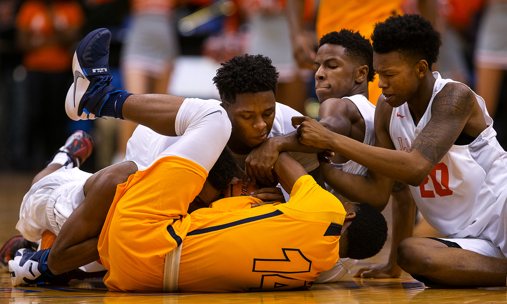 A pile of Lanphier defenders collapse onto Southeast's Trevyon Williams after he scooped up a loose ball during the City Tournament championship game at the Prairie Capital Convention Center Saturday, Jan. 23, 2016. Ted Schurter/The State Journal-Register