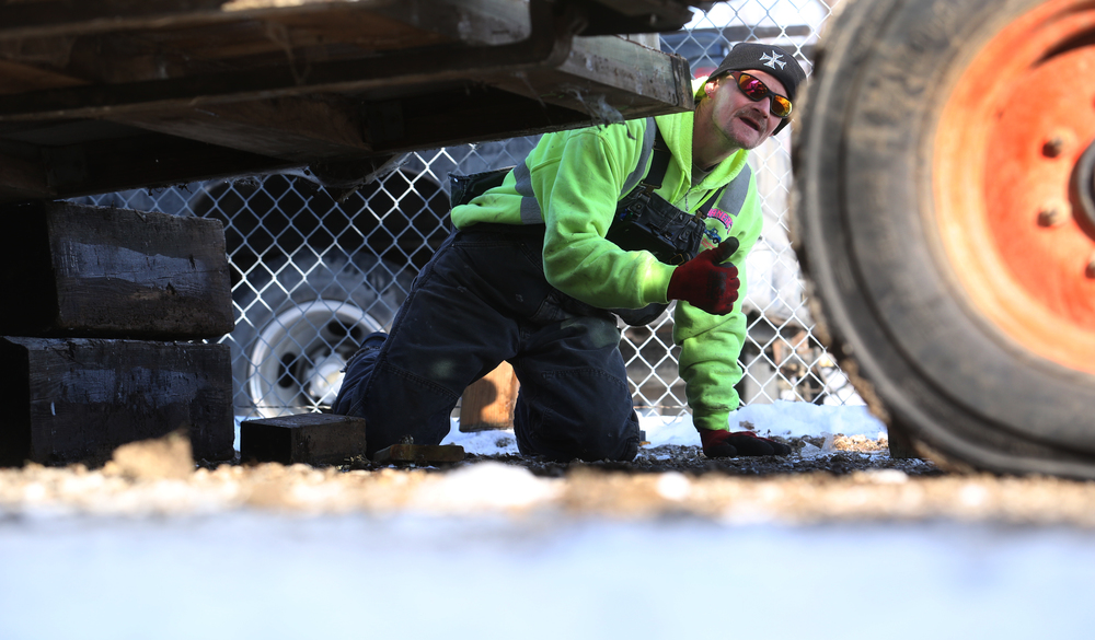 Shaner's Towing employee Travis Childers gives the thumbs before the Mahan's building was temporarily placed on large timbers before placement on the flatbed trailer for the move. David Spencer/The State Journal-Register