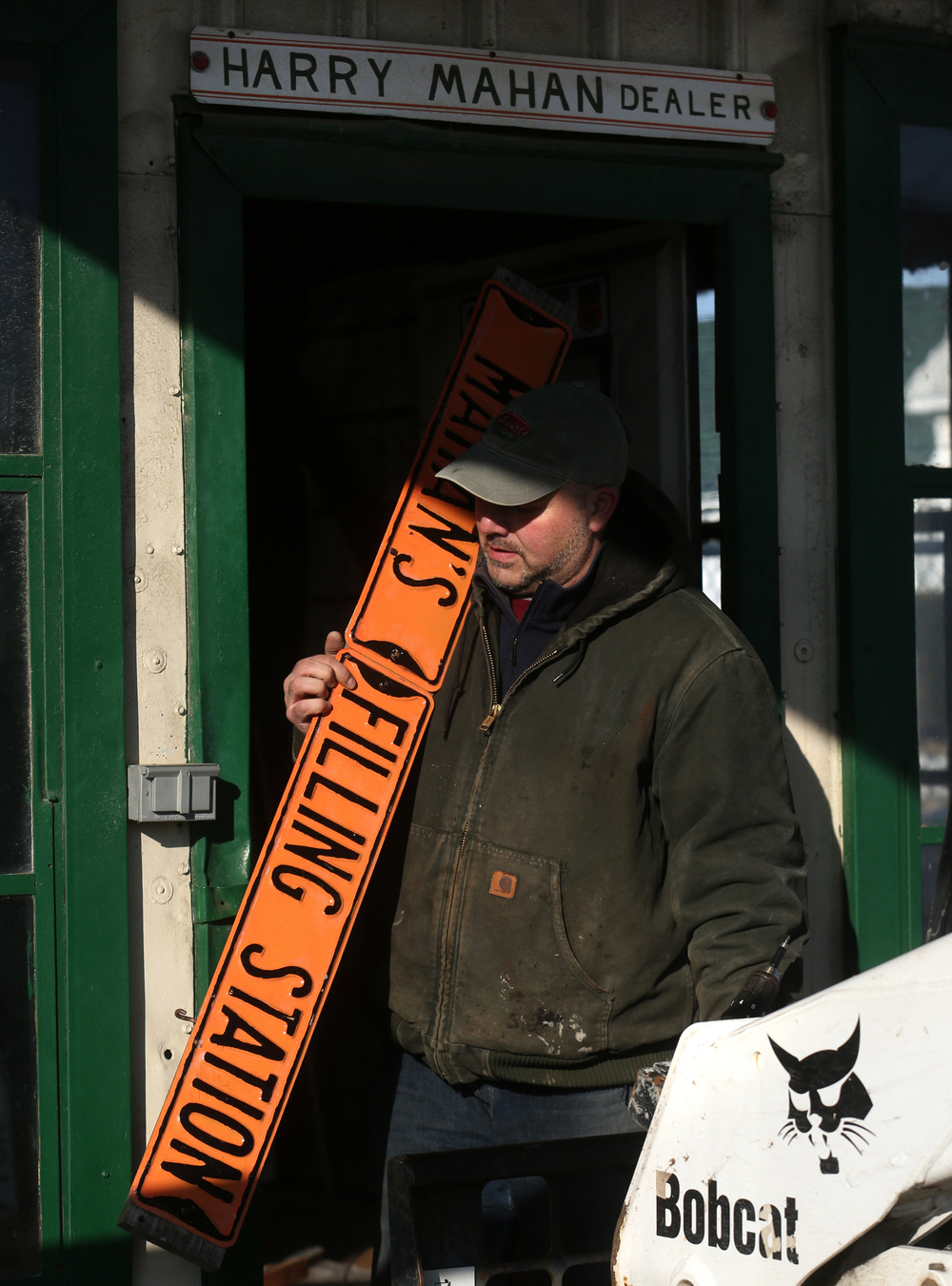 Building owner Jeff Fulgenzi retrieves the metal Mahan's Filling Station sign from inside the building before it was placed on the flatbed truck for the move. David Spencer/The State Journal-Register
