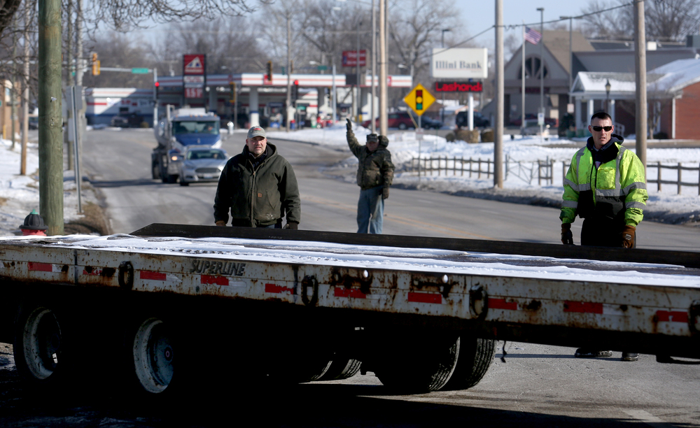 Traffic is held up as the long Shaner's Towing trailer guided by driver Jeremy Brozio is backed-up into the former Shea's Museum lot where the Mahan's building would be loaded onto it. David Spencer/The State Journal-Register