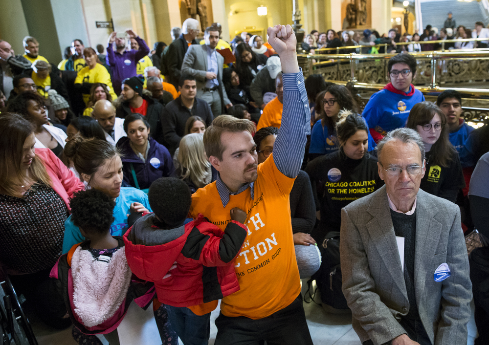 "Alex Wiesendanger, center, of Chicago, Ill., holding his foster son, protests outside Illinois Gov. Bruce Rauner's office after the State of the State address at the Illinois State Capitol, Wednesday, Jan. 27, 2016, in Springfield, Ill.  ""We're calling for a fair budget with revenues to fund the desperately needed services, including my son's health care and my daughters education,"" said Wiesendanger. Many groups gathered outside the house chambers chanting in protests that could be heard during Rauner's address. Justin L. Fowler/The State Journal-Register"