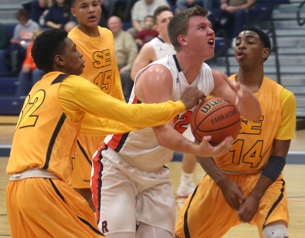 Southeast defenders Evan Meek at left and Trevyon Williams at right sandwich Rochester player Dan Zeigler as he tries to shoot the ball Friday. David Spencer/The State Journal Register