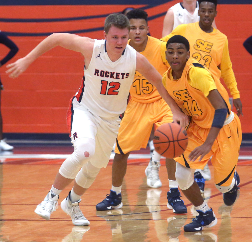 Rochester player Dan Zeigler at left and Southeast player Trevyon Williams go after a loose ball. David Spencer/The State Journal Register