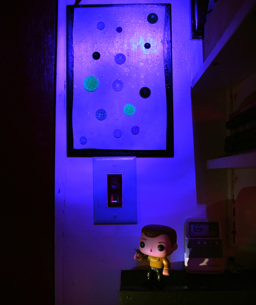 Funky planetary artwork at upper left created by Les Blain's granddaughter Emma hangs in the mancave above a customized lightswitch seen below it, and toy figurine of Capt. Kirk at bottom photographed on Friday, Jan. 29, 2016. David Spencer/The State Journal Register