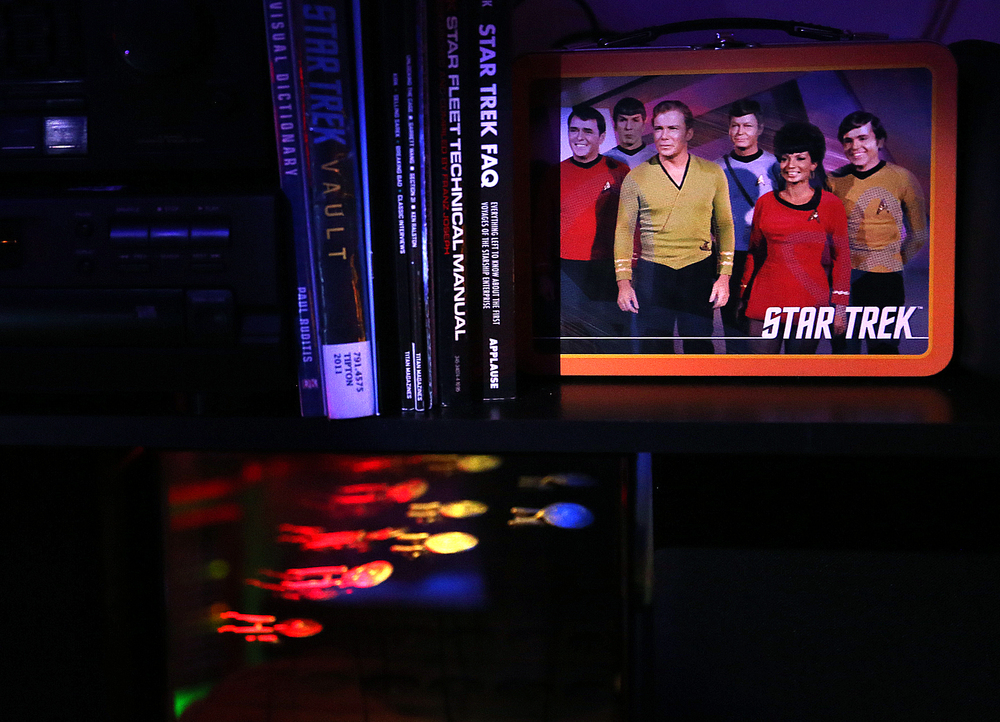 A stack of Star Trek related books, including one for the Star Fleet Technical Manual and Star Trek FAQ are arranged on a shelf next to a Star Trek lunch box in the mancave, photographed on Friday, Jan. 29, 2016. David Spencer/The State Journal Register