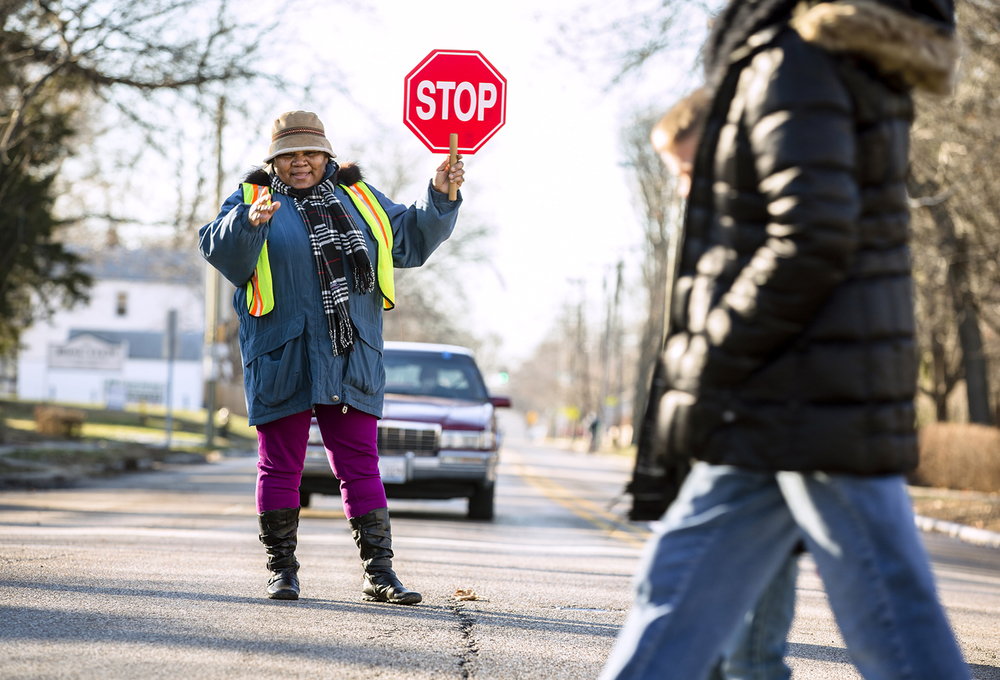 Dubois Elementary School crossing guard Connie Matthews heads out to the middle of the intersection of West Monroe Street and South Lincoln Avenue to stop traffic to allow for parents and children to cross safely on their way home from school. Matthews is a well known fixture of the intersection for those that use it daily as she will give a wave and a smile to all that pass through it. Justin L. Fowler/The State Journal-Register
