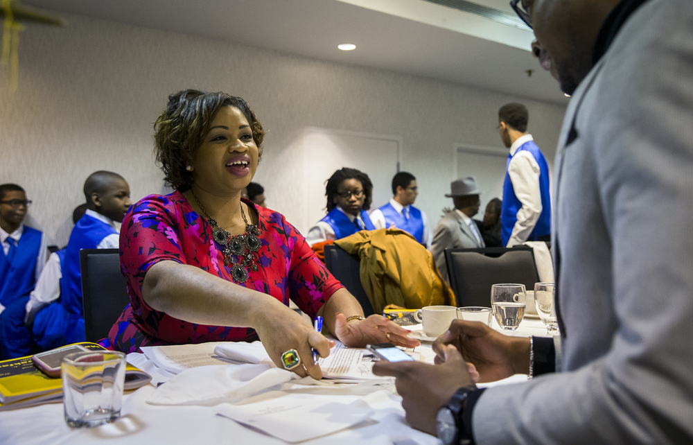 """Khalilah Brown-Dean, Associate Professor of Political Science at Quinnipiac University, signs a program for Justin Rose, right, after her remarks at the 41st annual Martin Luther King Jr. memorial breakfast, put on by Frontiers International Springfield Club at the Wyndham City Centre, Monday, Jan. 18, 2016, in Springfield, Ill. """"She is a phenomenal women and I'm thankful for her being here today,"""" said Rose. Justin L. Fowler/The State Journal-Register"""