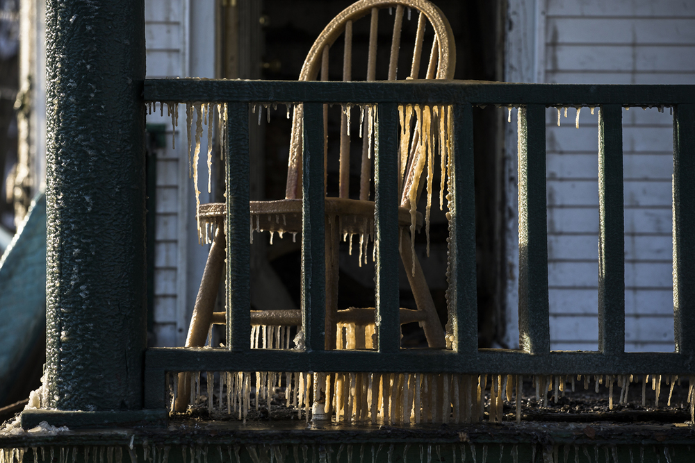 """A chair and the front porch of a two story home are covered in ice the morning after Springfield firefighters battled a blaze that gutted the structured in the 100 block of East Allen Street, Thursday, Jan. 21, 2016, in Springfield, Ill. Firefighters were called to the scene around 10:30 p.m to reports of a fire on the rear of the home. Two adults and two children escaped from the home unharmed and the cause of fire is currently under investigation. """"Anything that that gets spray on it will get a coating of ice,"""" said Chief Barry Helmerichs of the weather conditions. """"When it's cold and it's slick it's always tough."""" The construction of the home, when the fire spread to void spaces in the second floor, also hampered firefighters in extinguishing the blaze. Justin L. Fowler/The State Journal-Register"""