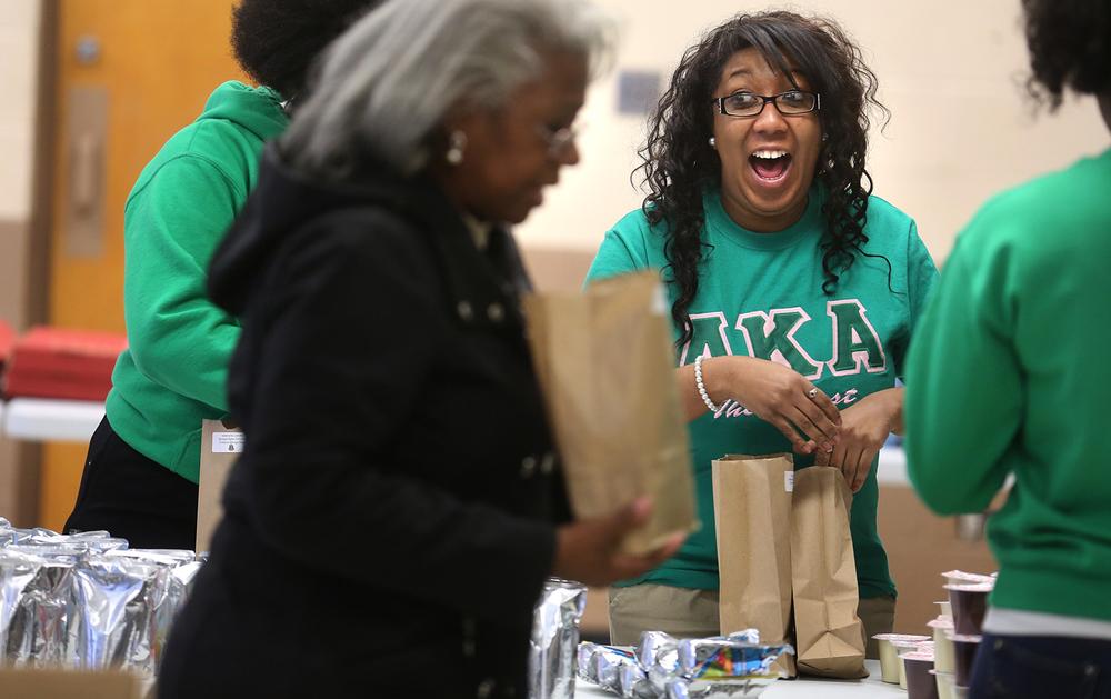 """Erica Austin, Nu Omicron Omega Chapter President, was having a fun time with her fellow volunteer chapter members filling individual bags with items including pudding, packaged juice, popcorn, macaroni and cheese, oatmeal and other non-perishable foodstuffs. Approximately 300 Springfield students in need attending five elementary schools: Hazel Dell, Harvard Park, Southern View, Lake Town and Matheny-Withrow will be the recipients of food bags this coming Friday packed by members of the Nu Omicron Omega Chapter of Alpha Kappa Alpha Sorority. The group's """"Pack-A-Sack 4 Kids"""" project took place in the church hall of Union Baptist Church in Springfield on Monday, Jan. 18, 2016. The MLK Day service project combats childhood hunger. David Spencer/The State Journal-Register"""