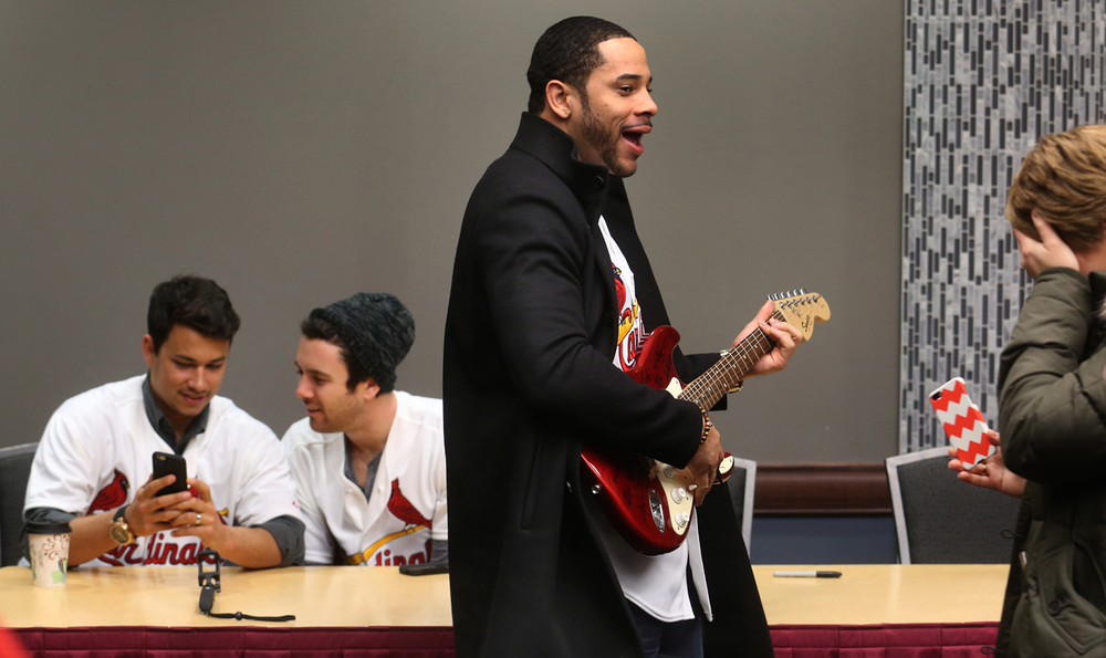 """Cardinals outfielder Tommy Pham has fun """"playing"""" a guitar he and other members of the team signed before the start of the Caravan that would be given away during a raffle at the event. At left in background are players Marco Gonzales at left and Tim Cooney. The 2016 Cardinals Caravan stopped off at the Prairie Capital Convention Center on Monday, Jan. 18, 2016, in Springfield. Current players and alumni attending were outfielder Tommy Pham, pitchers Tim Cooney, Marco Gonzales and Arturo Reyes, current third base coach Jose Oquendo, and former player and current scout Kerry Robinson. David Spencer/The State Journal-Register"""