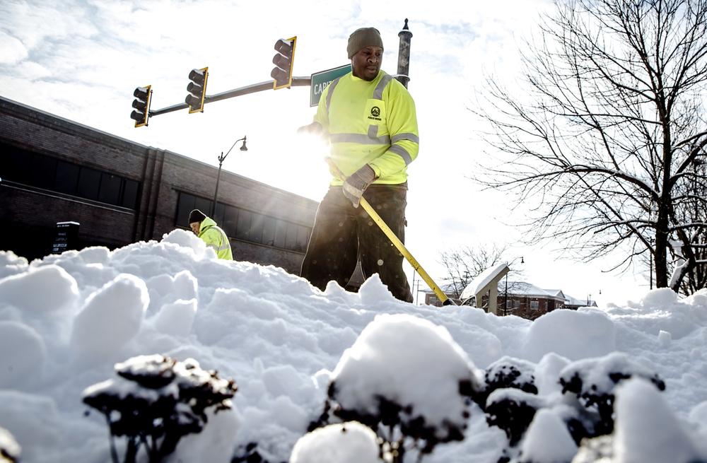 """Harvey Richards, a lead foreman with Public Works, clears out the sidewalks along the intersections of Capitol Avenue after 4.5"""" of snow fell overnight across the area, Wednesday, Jan. 20, 2016, in Springfield, Ill. Justin L. Fowler/The State Journal-Register"""